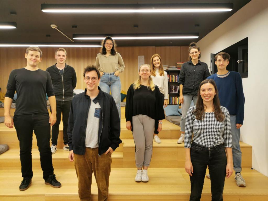 Neun Personen stehen auf Stufen mit Abstand im Raum